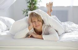 Mooi meisje in de ochtend in bed Stock Afbeelding