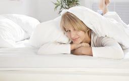 Mooi meisje in de ochtend in bed het glimlachen Stock Afbeeldingen