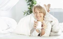 Mooi meisje in de ochtend in bed met kop Royalty-vrije Stock Afbeelding
