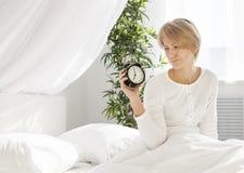Mooi meisje in de ochtend, die op het bed zitten Stock Afbeelding