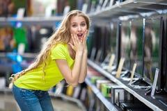 Mooi meisje in de opslag met TVs die prijzen benieuwd zijn royalty-vrije stock foto's