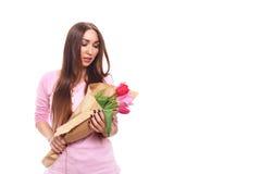Mooi meisje in de roze kleding met bloementulpen in handen op een witte achtergrond Geïsoleerd op wit royalty-vrije stock fotografie