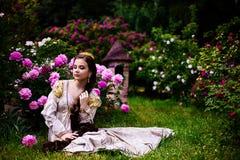 Mooi meisje in de tuin met bloemen in prinseskleding Stock Foto's