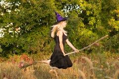 Mooi meisje in de vliegen van het heksenkostuum op bezemsteel Stock Foto
