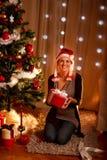 Mooi meisje dichtbij de holdingsgift van de Kerstboom royalty-vrije stock afbeeldingen
