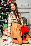 Mooi meisje dichtbij een Kerstboomzitting op een stuk speelgoed hert Een lo Royalty-vrije Stock Fotografie