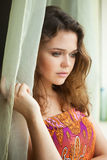 Mooi meisje dichtbij venster royalty-vrije stock afbeelding