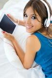 Mooi meisje die aan muziek met tablet op bank thuis luisteren Stock Afbeeldingen