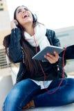 Mooi meisje die aan muziek in stad luisteren Stock Foto's