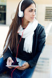 Mooi meisje die aan muziek in stad luisteren Stock Fotografie