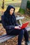 Mooi meisje die aan notitieboekje in zonnig de herfstpark werken stock afbeelding