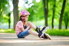 Mooi meisje die aan rolschaats op mooie de zomerdag leren in een park Stock Afbeelding