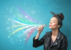 Mooi meisje die abstracte kleurrijke bellen en lijnen blazen Stock Afbeelding