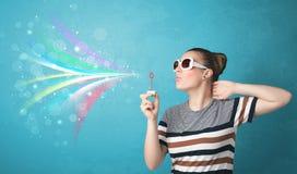 Mooi meisje die abstracte kleurrijke bellen en lijnen blazen Royalty-vrije Stock Afbeeldingen