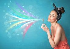 Mooi meisje die abstracte kleurrijke bellen en lijnen blazen Royalty-vrije Stock Fotografie
