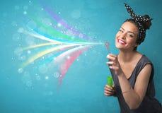 Mooi meisje die abstracte kleurrijke bellen en lijnen blazen Royalty-vrije Stock Foto's