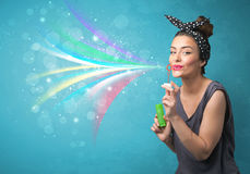 Mooi meisje die abstracte kleurrijke bellen en lijnen blazen Stock Fotografie