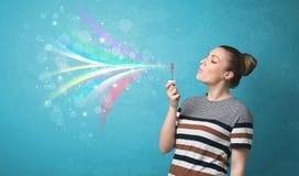 Mooi meisje die abstracte kleurrijke bellen en lijnen blazen Stock Foto