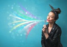 Mooi meisje die abstracte kleurrijke bellen en lijnen blazen Stock Foto's