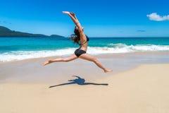 Mooi meisje die in bikinis op tropisch strand springen stock afbeelding