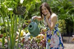 Mooi meisje die de installaties water geven royalty-vrije stock afbeeldingen