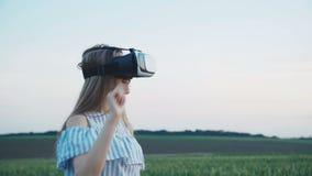 Mooi meisje die in de virtuele hoofdtelefoon van werkelijkheidsbeschermende brillen op het gebied imiteren stock video