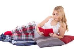 Mooi meisje die in die pyjama's boek lezen op wit wordt geïsoleerd Stock Foto