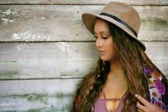 Mooi meisje die door een houten muur denken stock afbeelding