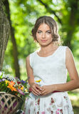 Mooi meisje die een aardige witte kleding dragen die pret in park met fiets hebben die een mooi mandhoogtepunt van bloemen dragen Royalty-vrije Stock Foto's