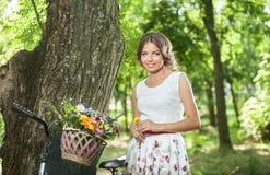 Mooi meisje die een aardige witte kleding dragen die pret in park met fiets hebben die een mooi mandhoogtepunt van bloemen dragen Stock Fotografie