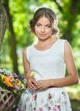 Mooi meisje die een aardige witte kleding dragen die pret in park met fiets hebben die een mooi mandhoogtepunt van bloemen dragen Stock Afbeeldingen