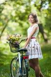 Mooi meisje die een aardige witte kleding dragen die pret in park met fiets hebben Gezond openluchtlevensstijlconcept Uitstekend  stock foto's