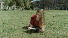 Mooi meisje die een boek op campusgazon lezen stock videobeelden