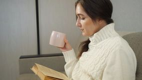 Mooi meisje die een boek thuis lezen en koffie op de bank drinken stock videobeelden