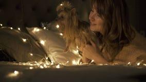 Mooi meisje die een de decoratiestuk speelgoed van de Kerstmissneeuwvlok op bed spinnen Zij is gelukkig stock video