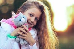 Mooi meisje die een favoriet gevuld dier koesteren - een kat voor royalty-vrije stock foto