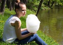 Mooi meisje die een gesponnen suiker houden Stock Afbeeldingen