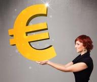 Mooi meisje die een groot 3d gouden euro teken houden Stock Foto's