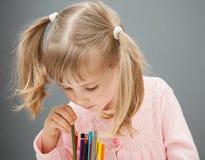 Mooi meisje die een potlood kiezen stock afbeeldingen