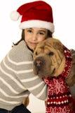 Mooi meisje die een santahoed dragen die een Shar Pei-hond koesteren Stock Afbeeldingen