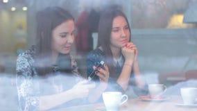 Mooi meisje die een smartphonemeisje in koffie tonen stock videobeelden