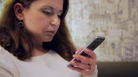 Mooi meisje die een tekst op uw mobiele telefoon lezen stock videobeelden