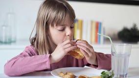 Mooi meisje die een volledige hamburger thuis eten stock video