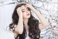 Mooi meisje die en bij tot bloei komende boom in de tuin over witte achtergrond ontspannen genieten van stock foto's