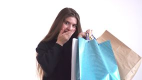 Mooi meisje die en pakketten met aankopen glimlachen houden en verrast voorraad in kleinhandelskettingen stock footage