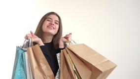 Mooi meisje die en pakketten met aankopen glimlachen houden en verrast voorraad in kleinhandelskettingen stock videobeelden