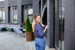 Mooi meisje die en smartphone in stad lopen houden Royalty-vrije Stock Foto