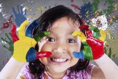 Mooi meisje die geschilderde handen tonen Stock Foto's