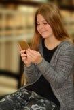 Mooi meisje die haar celtelefoon met behulp van Royalty-vrije Stock Afbeelding