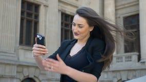 Mooi meisje die haar haar in langzame motie wegknippen terwijl zij die smartphone voor selfie gebruiken stock footage